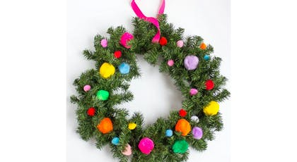 Une couronne de Noël en branches de sapin et pompons