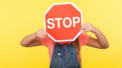petite fille tenant un panneau stop