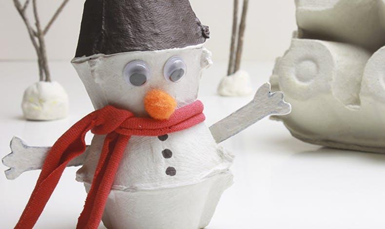 Un bonhomme de neige avec une boite d'œufs