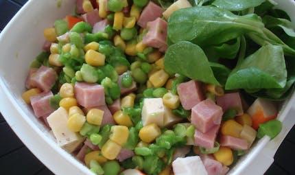 Une salade de maïs, avec du jambon, des petits pois et du surimi