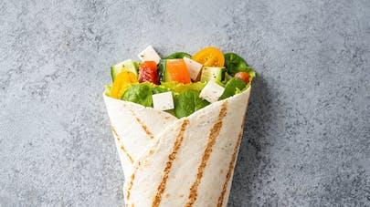 Wrap végétarien avec salade, tomates cerises, poivrons,       fêta