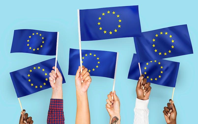 Mains levées tenant des drapeaux européens