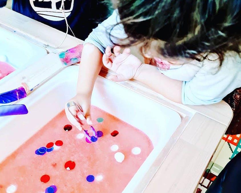 fille qui joue avec un bac sensoriel pour découvrir le sang