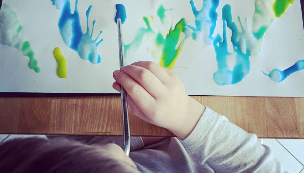 enfant qui peint avec une paille et de la peinture diluée