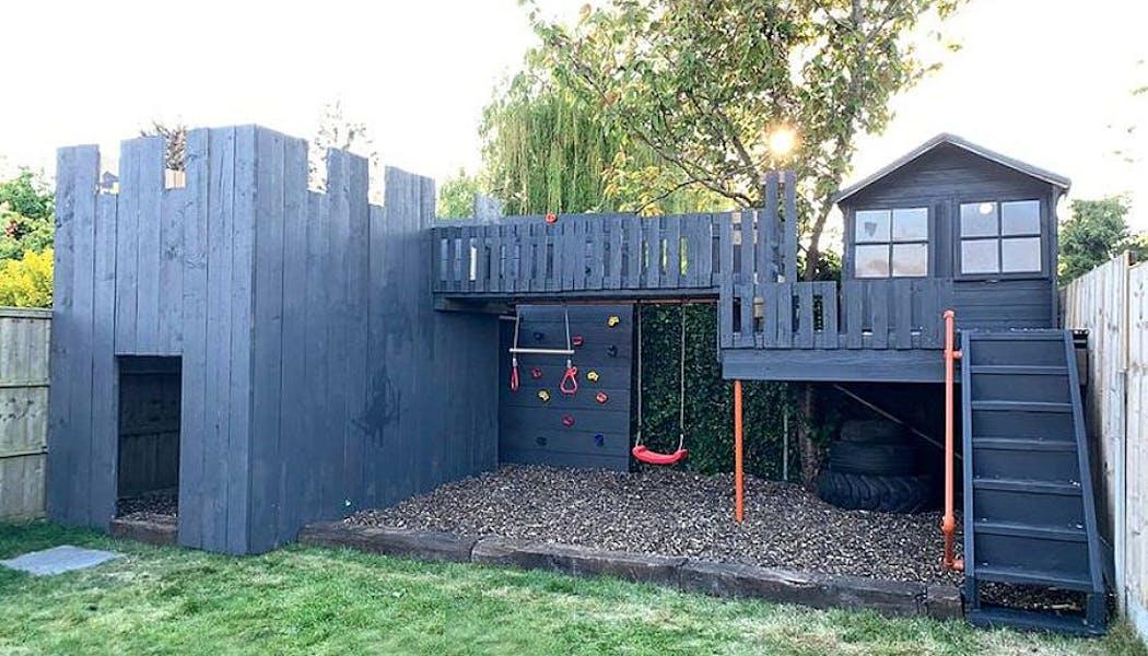 cabane ressemble à un château fort avec toboggan, balançoire et mur d'escalade