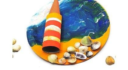 un phare et une plage, faits avec une assiette en carton et un rouleau de papier toilette