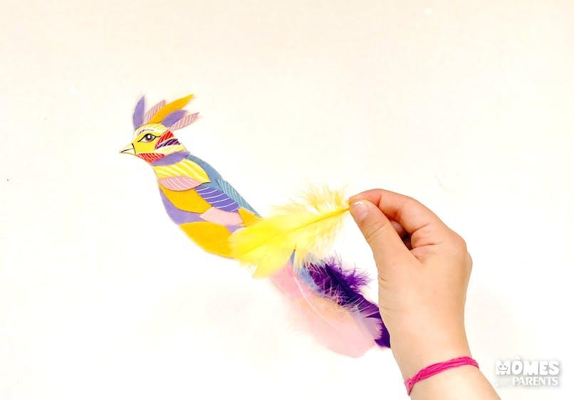 Dessiner l'œil et le bec de l'oiseau puis coller des plumes sur la queue.